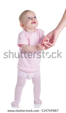 Cute baby learning to walk by holding his mother's hands