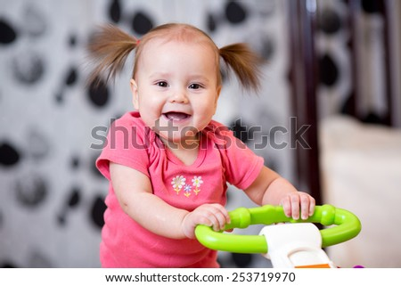 Cute baby learning to walk with support - stock photo