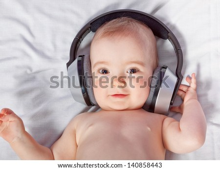 Cute baby listens to music through headphones. Close-up.