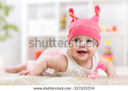 Cute baby little girl in funny hat having fun - stock photo