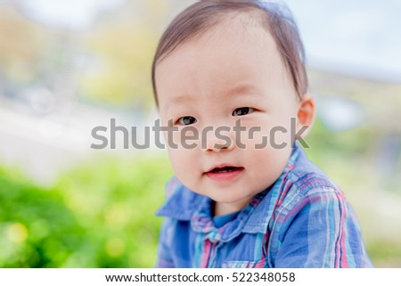 cute baby look somewhere and smile happily in the park, asian