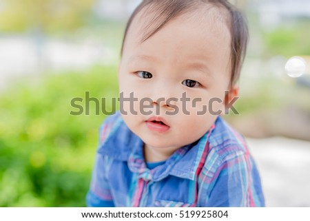 cute baby look you and smile happily in the park, asian
