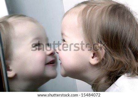Cute baby looking into mirror, laughing