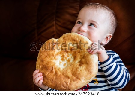Cute baby looking up and eating unleavened wheat cake (lavash) in hands - stock photo