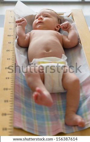 Cute baby lying in height meter in a clinic - stock photo