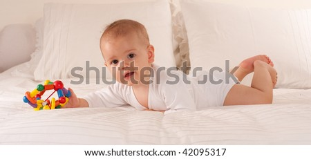 Cute baby lying on a bed holding a colourful toy
