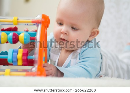 Cute baby lying on belly  on soft surface and intently playing with her colorful toys. Close up portrait - stock photo