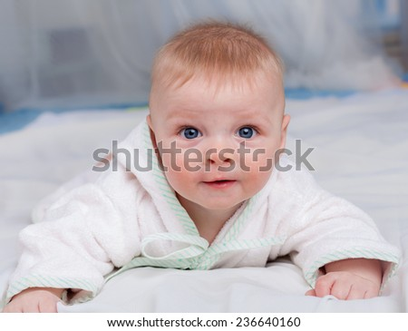 Cute baby lying on soft sofa and looking at camera - stock photo
