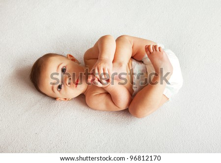Cute baby lying on white blanket and holding legs