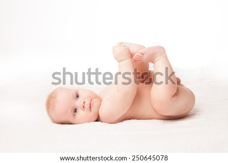 Cute baby lying on white blanket touching his feet. Isolated over white background.