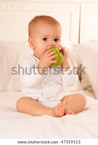 Cute baby on a bodysuit biting a green apple