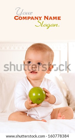 Cute baby on a bodysuit holding a green apple