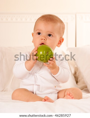 Cute baby on a bodysuit holding a green apple - stock photo