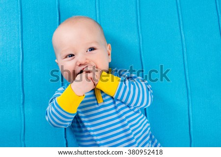 Cute baby on blue knitted blanket. Teething infant playing with colorful toy. Little boy in bed after nap. Bedding and textile for nursery and young children. Kids sleep wear. Newborn child at home. - stock photo