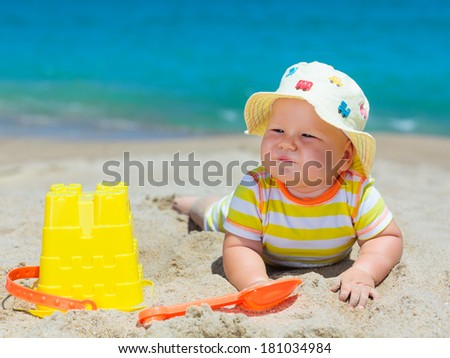 Cute baby on the tropical beach playing toys - stock photo