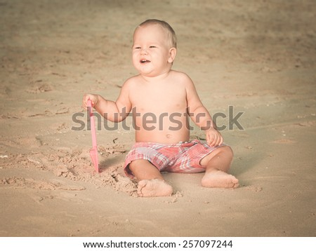 Cute baby on the tropical beach playing toys. Toned - stock photo