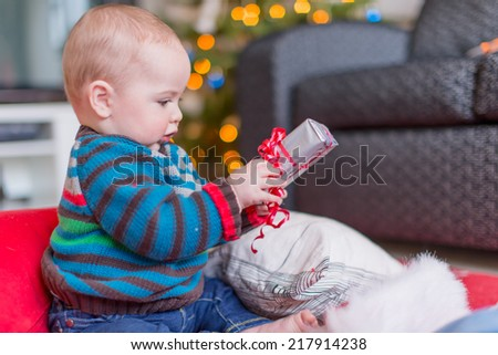 Cute baby opening a Christmas gift - stock photo