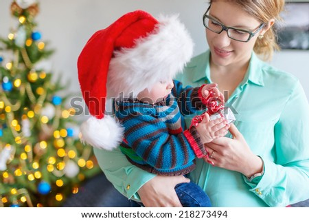 Cute baby opening a gift from his mother - stock photo