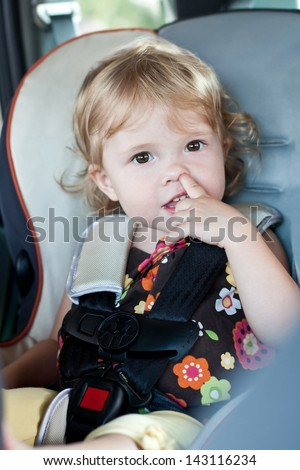 Cute baby picks his nose while sitting in the car seat - stock photo