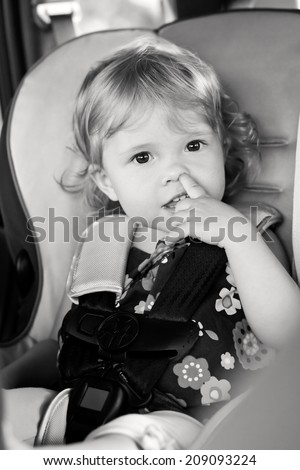 Cute baby picks his nose while sitting in the car seat ( black and white ) - stock photo