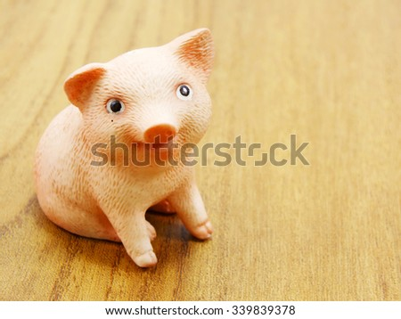 cute baby piglet doll on wooden background