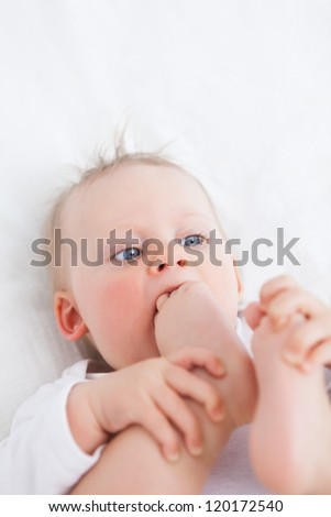 Cute baby placing her foot on her mouth while lying on a blanket - stock photo