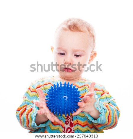 Cute baby play with ball on white backdrop - stock photo