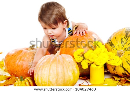 Cute baby playing among ripe pumpkins