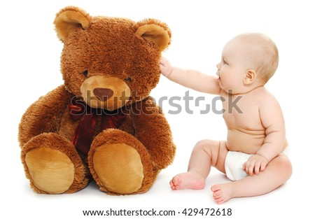 Cute baby playing with big teddy bear on white background - stock photo