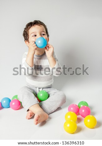 Cute baby playing with colored balls