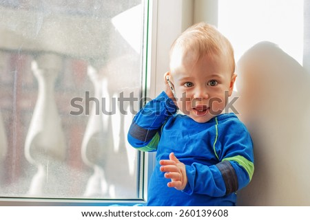 Cute baby playing with mobile phone - stock photo