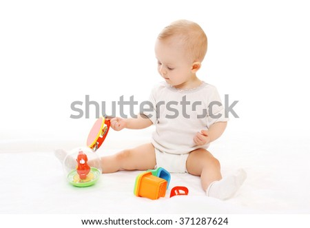 Cute baby playing with toys on white background