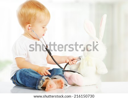 cute baby plays in doctor toy bunny rabbit and stethoscope - stock photo
