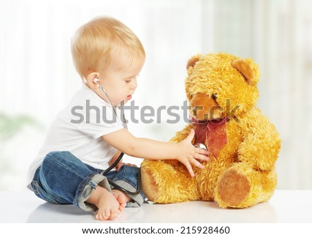 cute baby plays in doctor toy teddy bear and stethoscope - stock photo