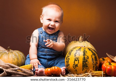 Cute baby posing on the background of pumpkins. Thanksgiving greetings - stock photo