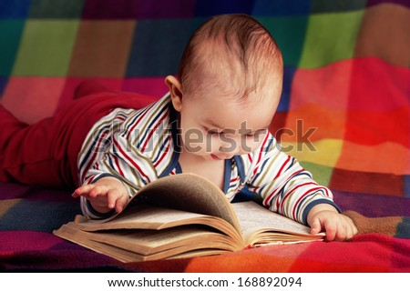 cute baby reading book on colorful background - stock photo