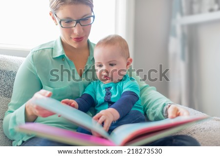 Cute baby reading with his mother - stock photo