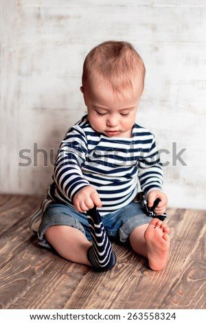 Cute baby-sailor in stripped vest taking off his second sock - stock photo