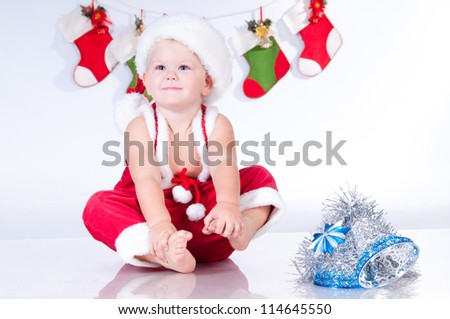 Cute baby Santa Claus with garlands of Christmas bootee - stock photo
