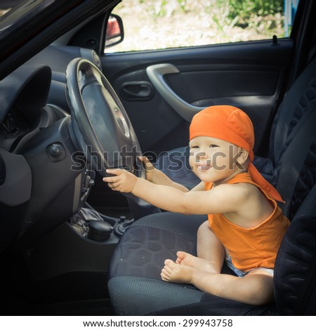 Cute baby sitting in a car - stock photo