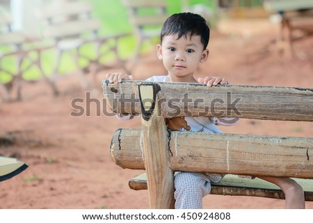 Cute baby sitting on a bench in the morning with freedom. - stock photo