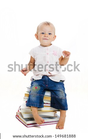 Cute baby sitting on books on white background - stock photo
