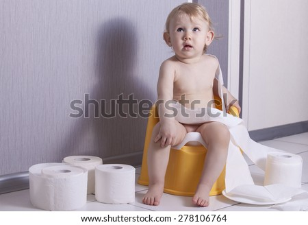 Cute baby sitting on chamber pot with toilet paper rolls - stock photo