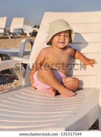 cute baby sitting on  sun lounger - stock photo