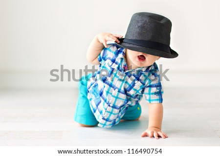 Cute baby sitting on the floor in a hat - stock photo