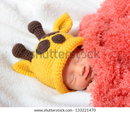cute baby sleeping in funny hat and smiling in sweet dreams, beautiful kid's face closeup - stock photo