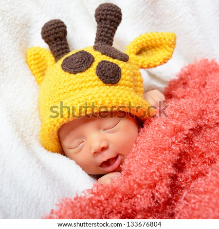 cute baby sleeping in funny yellow giraffe hat and smiling in sweet dreams, beautiful kid's face closeup - stock photo