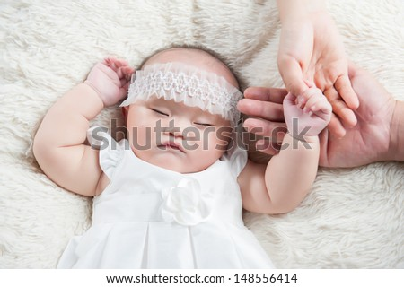 Cute baby sleeping on a white blanket. Childhood in parents hands - stock photo