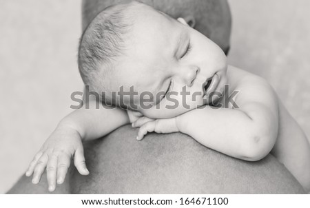 Cute baby sleeping on his father's shoulder ( black and white ) - stock photo