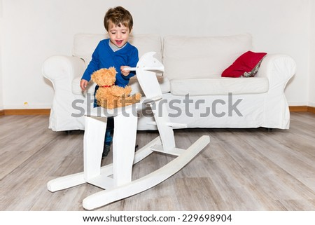 Cute baby smiling and playing with a white rocking horse in the living room